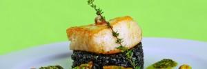 Chilean sea bass sobre risotto de sepia y frito de puerro, acompañado de mini verduras al horno con pesto de albahaca y pistachos.